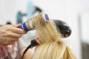 Blowing drying blond hair with a round brush photo