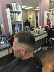 Man hair cut close sides, combed back top